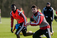SWANSEA, WALES - JANUARY 28: Bafetibis Gomis of Swansea City and Jordi Amat of Swansea City run forwards during training  on January 28, 2015 in Swansea, Wales.