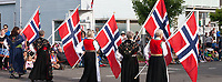 Norwegian women wearing traditional dresses marching with Norway flags, 17th of May Parade 2016, Ballard, Seattle, WA, USA.