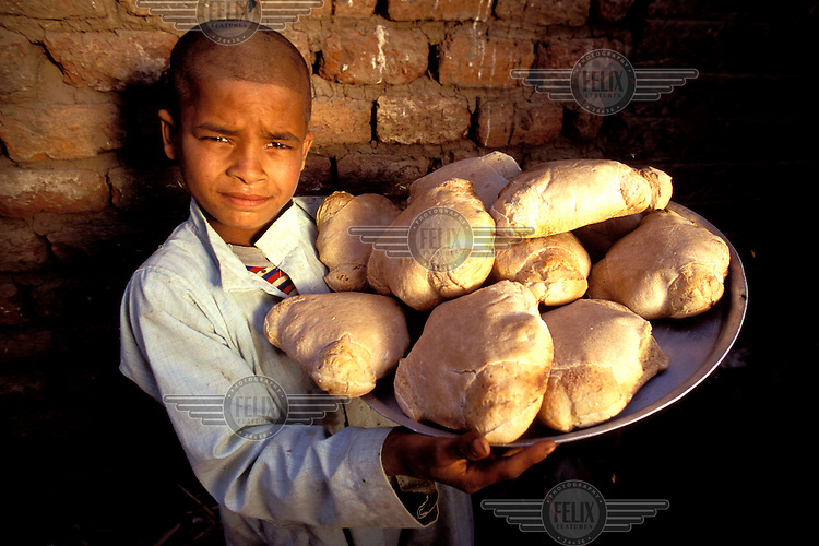 © Giacomo Pirozzi / Panos Pictures..EGYPT..A boy shows off bread made at his mother's bakery, which was set up with the help of a micro-credit loan.