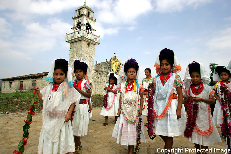 Naua Indian children in full-colored clothes walk past the church in their village of Ayotzinapan, Puebla. Photo by Heriberto Rodriguez/ CGEIB