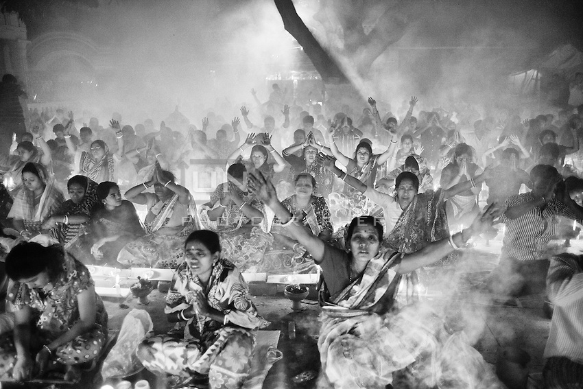 The faithful pray raising their hands to the sky while thick clouds of incense raise into the air in front of Shri Shri Lokenath Brahmachari Ashram temple for the Kartik Brati or Rakher Upobash religious festival in Barodi,  Near Dhaka, Bangladesh