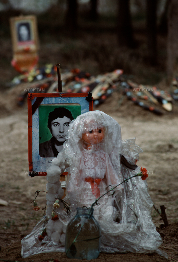 Azerbaijan, Karabakh, Aghdam, 1992<br /> On the night of February 26, 1992, the Armenian armed forces committed a massacre in Khojaly, a small town in the Nagorno-Karabakh region of the Republic of Azerbaijan. At least 613 people were killed; 1275 taken hostage, 150 went missing.  The brutality of Armenian forces during the occupation of Khojaly was documented by Human Rights Watch, Amnesty International, &ldquo;Memorial&rdquo; Society, the New York Times, Newsweek, Washington Post, Agence France Presse and other human rights and media organizations.After the Khojaly massacre, the International Red Cross organized a local cease-fire to allow both sides to exchange prisoners and to allow the Red Cross to bring the corpses of Azerbaijanis killed in Khojaly to Aghdam. The bodies were brought to the mosque in Aghdam, which served as a morgue for families to visit and search for their loved ones who had disappeared. Next to the mosque, a makeshift cemetery was created for the families to bury their loved ones.Dolls are placed on the graves of youths who were killed before ever being married.<br /> <br /> Azerbaidjan, Karabakh, Aghdam, Fevrier 1992 <br /> Dans la nuit du 26 fevrier 1992, les forces armees armeniennes commetent  un massacre a Khodjali, petite ville de la region du Haut-Karabakh de la Republique d'Azerbaidjan. Plus de 613 personnes sont tuees; 1275 otages, 150 disparus.  La brutalite des forces armeniennes pendant l&rsquo;occupation de Khodjali a ete documentee par Human Rights Watch, Amnesty International, &laquo;&nbsp;Memorial&nbsp;&raquo; Society, the New York Times, Newsweek, Washington Post, l&rsquo;Agence France Presse et d&rsquo;autres ligues de defense des droits humains et organisations mediatiques. Apres le massacre de Khodjali, la Croix-Rouge internationale a organise un cessez-le-feu local pour permettre a la Croix Rouge de rendre les corps des Azerbaidjanais morts a Khodjali a ceux qui ont survecu au massacre et qui ont trouve refuge dans la vi