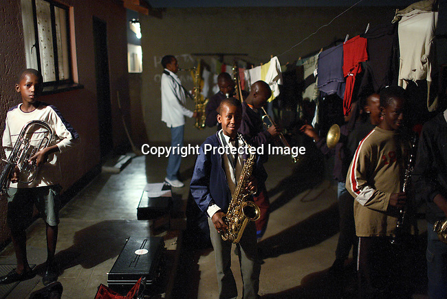 Members of a brass band regearses after dark in a back yard in Soweto.l