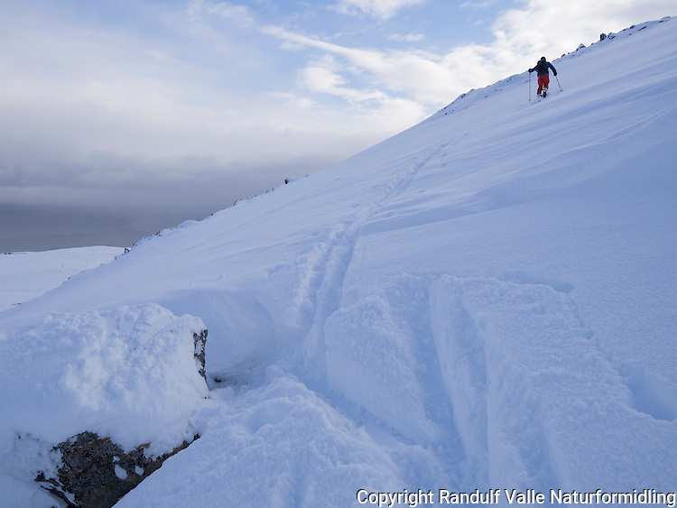 Mann på tur opp Eidvågtind på Seiland. ---- Man skiing up mountain.