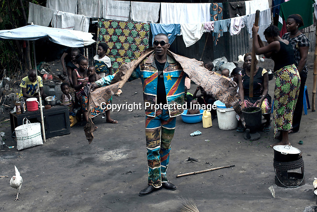 "KINSHASA, DEMOCRATIC REPUBLIC OF CONGO - FEBRUARY 12: Papa Griffe, a senior and a leader of the Sapeurs poses for pictures in a traditional outfit in the Mombele area where he lives on February 12, 2012 in Kinshasa, DRC. The word Sapeur comes from SAPE, a French acronym for Société des Ambianceurs et Persons Élégants or Society of Revellers and Elegant People and it also means, to dress with elegance and style"". Most of the young Sapeurs are unemployed, poor and live in harsh conditions in Kinshasa,  a city of about 10 million people. For many of them being a Sapeur means they can escape their daily struggles and dress like fashionable Europeans. Many hustle to build up their expensive collections. Most Sapeurs could never afford to visit Paris, and usually relatives send or bring clothes back to Kinshasa. (Photo by Per-Anders Pettersson)"