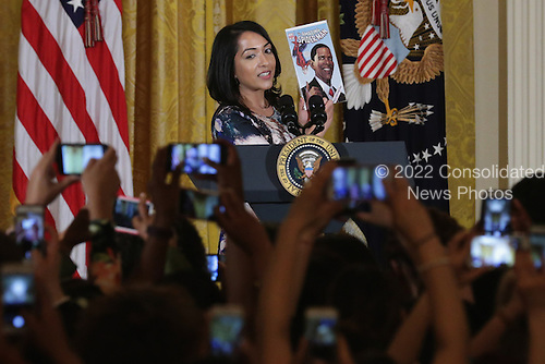 Marvel comic book creator and editor Sana Amanat holds up a comic book featuring U.S. President Barack Obama as she introduces him at a reception for Women's History Month in the East Room of the White House March 16, 2016 in Washington, DC. Obama announced the White House will host a summit on The United State of Women this May. According to the White House, the summit will &quot;highlight the advances we have made in the United States and across the globe and to expand our efforts on helping women confront the challenges they face and reach for their highest aspirations.&quot; <br /> Credit: Chip Somodevilla / Pool via CNP