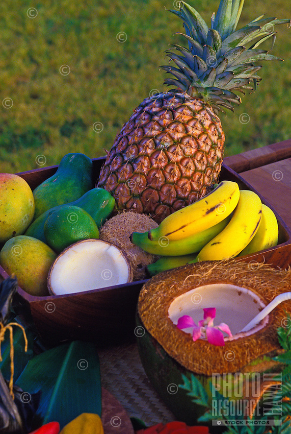 A delectable assortment of just picked from the tree tropical fruits arranged inside a dark wood tray and accompanied by a halved freshly husked coconut with serving spoon and orchid blossom. Shot outdoors against a grassy background.