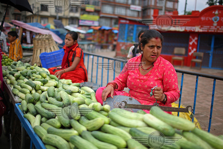 Women selling cucumbers and other vegetables on a street near New Road area in Kathmandu.