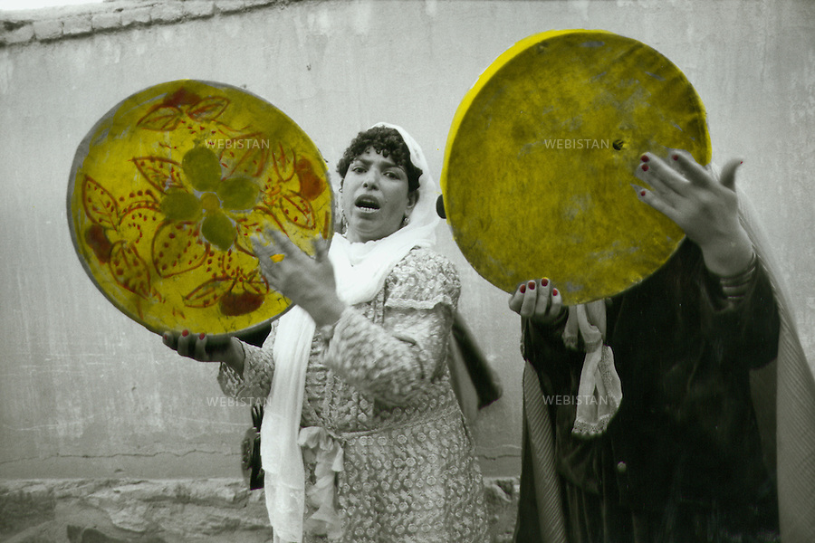 2002. Afghanistan. Kabul. Two women sing to the sound of their tambourine during a wedding ceremony. Afghanistan. Kaboul. Deux femmes chantent au son de leur tambourin lors d'une cérémonie de mariage.