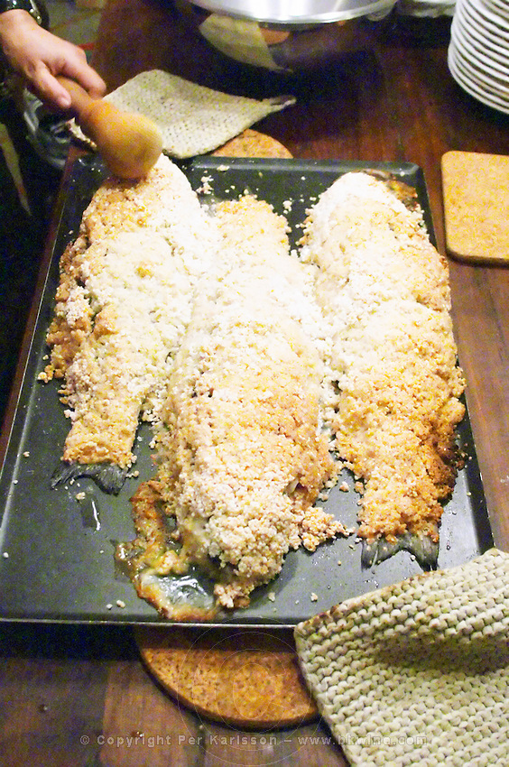 How to prepare fish baked in the oven in salt crust (en croute de sel), recipe, series of pictures: three fish covered in salt crust after being baked in the oven, a man breaking the salt crust with a club Clos des Iles Le Brusc Six Fours Cote d'Azur Var France