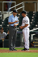 First base umpire Travis Eggert explains a call to Salt River Rafters manager Tripp Keister (7) during an Arizona Fall League game against the Scottsdale Scorpions on October 13, 2015 at Salt River Fields at Talking Stick in Scottsdale, Arizona.  Salt River defeated Scottsdale 5-3.  (Mike Janes/Four Seam Images)