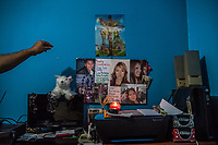 Carlos Saldana reaches to adjust the small shrine created in memory of his and Vicky Delgadillo's missing children in the bedroom of their home in Xalapa, Mexico on November 4, 2017. <br /> Photo Daniel Berehulak for The New York Times