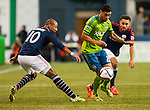 Seattle Sounders Lamar Neagle (27)  controls the ball against New England Revolution Teal Bunbury (10) and Kevin Alston (30) during an MLS match on March 8, 2015 in Seattle, Washington.  The Sounders beat the Revolution 3-0.  Jim Bryant Photo. ©2015. All Rights Reserved.
