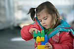 "A girl plays with blocks inside a ""child-friendly space"" in a refugee processing center in the Serbian village of Presevo, not far from the Macedonian border. Hundreds of thousands of refugees and migrants--including many children--have flowed through Serbia in 2015, on their way from Syria, Iraq and other countries to western Europe."