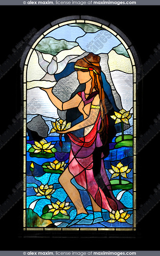 Decorative arched stained glass window showing a Cypriot girl with a water lily and a dove