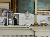 On the living room mantelpiece party invitations, a royal Christmas card and photographs of friends can be found propped against a 17th century oil painting