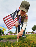 Garrett Van Roy, 11, places flags on the graves of veterans at the Lone Mountain Cemetery in Carson City, Nev., on Friday, May 25, 2012. Volunteers from the D.A.V., American Legion, Carson High School ROTC and Boy Scout Troop 145 placed more than 1,400 flags on the graves of veterans in honor of Memorial Day..Photo by Cathleen Allison