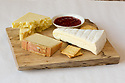 Three cheeses on a cutting board with crackers and fruit preserves