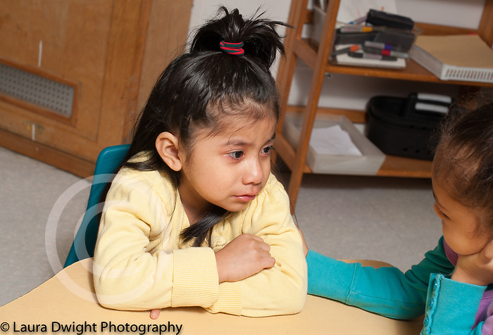 Education preschool 3 year olds girl listening to sad classmate