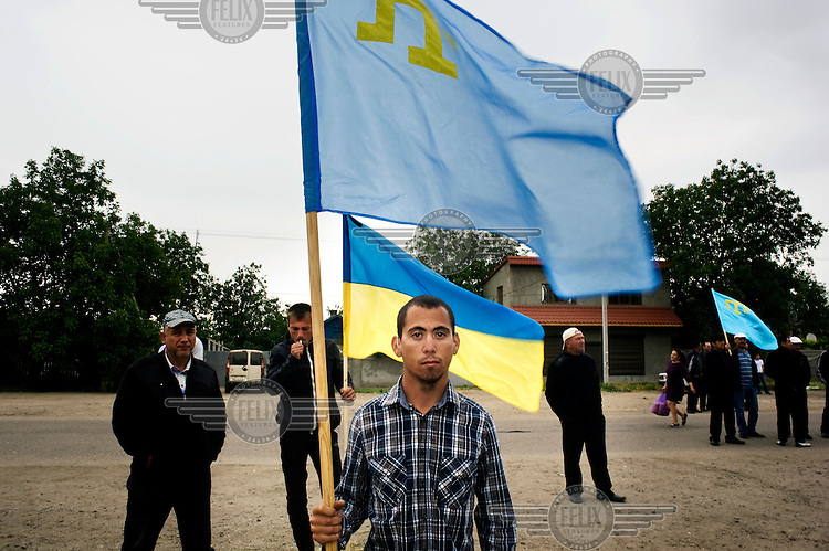 A Crimean Tatar man holds the flag of the Crimean Tatars while another holds the Ukrainian flag during a 70th anniversary commemoration ceremony remembering those Tatars who were deported by Stalin to central Asia in the 1940s.