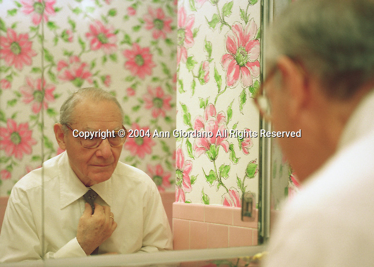 Retired Man Dressing in Suburban Bathroom with Flowered Wall Paper.
