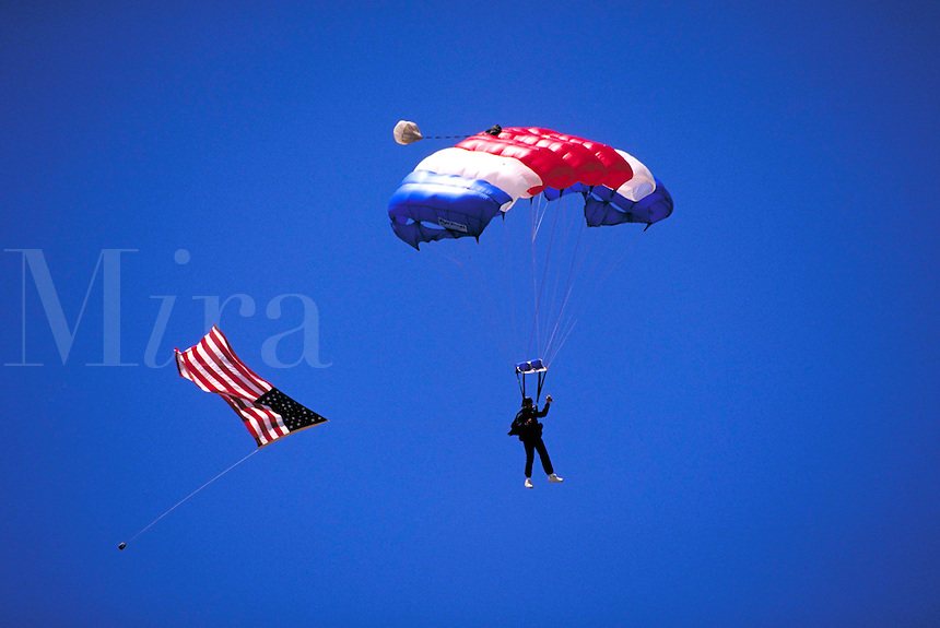 Skydiver Allen Silver descends with red, white and blue parachute; American flag trails behind him. Allen Silver. Watsonville California.