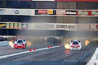 Feb 8, 2014; Pomona, CA, USA; NHRA funny car driver Bob Tasca III (right) races alongside Gary Densham during qualifying for the Winternationals at Auto Club Raceway at Pomona. Mandatory Credit: Mark J. Rebilas-