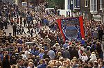 Durham Miners Gala. National Union of Mine Workers, Durham Area, Seaham Lodge banner. Children holding hands in a circle and dancing in front of the Silver Band 1980s UK