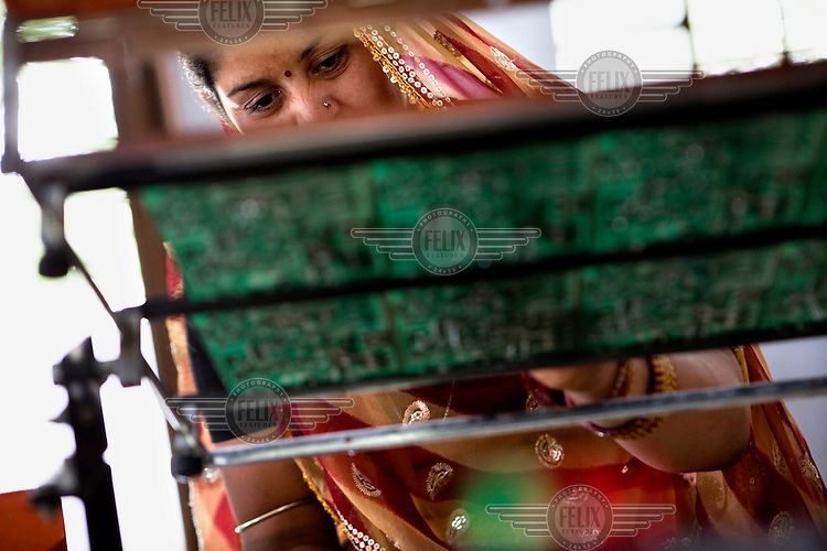 A student solders and assembles circuit boards during a solar engineering class at the Tilonia village Barefoot College (run by an NGO that provides education in rural communities).