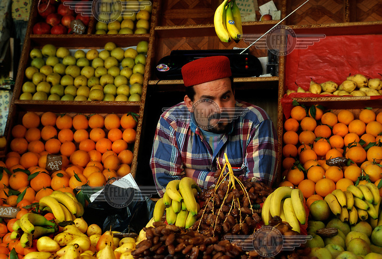 Fruit seller wearing a traditional Tunisian chechia hat.