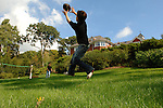 Boy leaps for fingertip catch of  football thrown by his brother in their backyard.