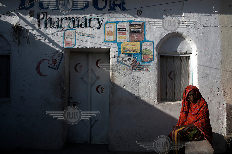 A woman waits for a pharmacy to open in Hargeisa.