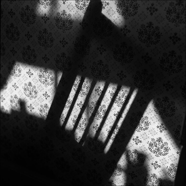 The shadow of a chair on wallpaper