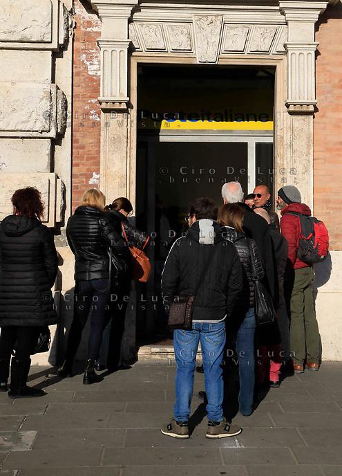 Persone in coda alle Poste presentazione della richiesta di Reddito di Cittadinanza