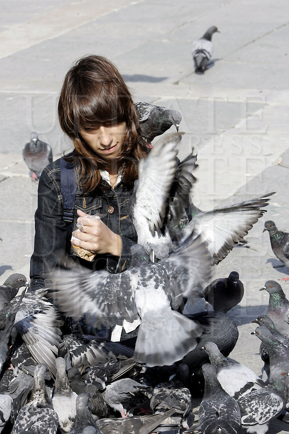 Una turista gioca con i piccioni in Piazza San Marco a Venezia.<br /> A tourist plays with pigeons in front of the Patriarchal Cathedral Basilica of St. Mark in Venice.<br /> UPDATE IMAGES PRESS/Riccardo De Luca