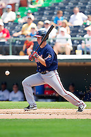 Todd Cunningham (9) of the Gwinnett Braves hits a check-swing ground ball against the Charlotte Knights at Knights Stadium on July 28, 2013 in Fort Mill, South Carolina.  The Knights defeated the Braves 6-1.  (Brian Westerholt/Four Seam Images)