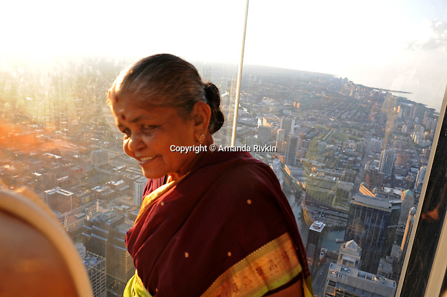 """An Indian woman is seen on the newly opened glass balconies """"The Ledge"""" at the Skydeck at the Sears Tower in Chicago, Illinois on July 6, 2009."""