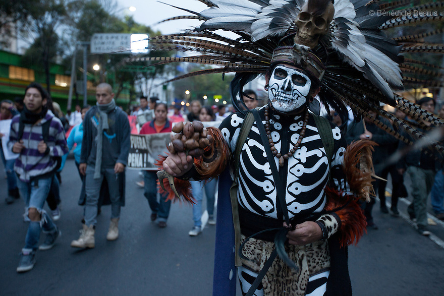 A protester dressed in an Aztec costume walks during a massive march in support of the 43 missing Ayotzinapa's students, on a day normally reserved for the celebration of Mexico's 1910-17 Revolution, in Mexico City, Mexico on November 20, 2014. Parents of the 43 missing students still do not believe the official line that the young men are all dead. Criticism of the government has intensified in Mexico and the country has been convulsed by protests. Many are demanding justice and that the search for the 43 missing students continue until there is concrete evidence to the contrary. Mexico officially lists more than 20 thousand people as having gone missing since the start of the country's drug war in 2006, and the search for the missing students has turned up other, unrelated mass graves.(Photo by BénédicteDesrus)