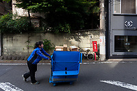 A woman working for Sagawa Express delivery company pushes a cart filled with parcels in a street in Ebisu, Tokyo, Japan. Friday June 8th 2018