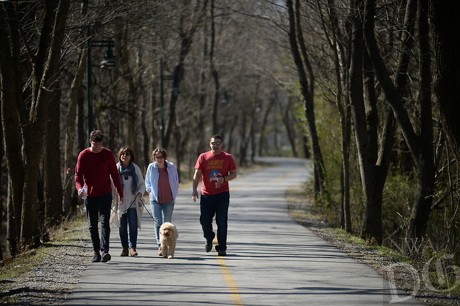 NWA Democrat-Gazette/ANDY SHUPE<br /> Nahum Payne (from left), Shawn Frick, Sydney Walsh and Jacob Meisenbacher, all coworkers at Creative in Fayetteville, walk Friday, March 22, 2019, with Jackson along the trail west of the Fayetteville Public Library. Voters will be asked April 9 to continue the city's 1-cent sales tax to pay for about $226 million in projects. Of that, about $30 million would go toward building an arts corridor and parking downtown. Part of the arts corridor plan includes turning the Fay Jones Parkland woods into a natural attraction with a canopy walk, trail connections and restored vegetation and streamside areas.