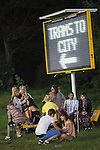 © Joel Goodman - 07973 332324 . 08/06/2013 . Heaton Park , Manchester , UK . Revellers sit below a temporary Trams to City sign in Heaton Park after the close of Day 1 . Day 1 of the Parklife music festival in Manchester on Saturday 8th June 2013 . Photo credit : Joel Goodman
