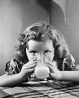 Girl drinking her milk.