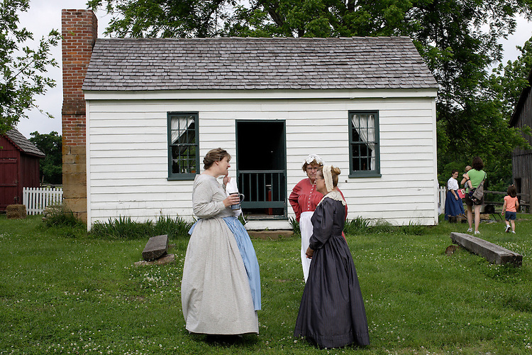 Missouri Town 1855 volunteers dressed in period clothing set the atmosphere while chatting in front of the blacksmith's house. This old Missouri town is located on the east side of Lake Jacomo in Fleming Park in Blue Springs, MO. Missouri Town 1855 is a collection of original mid-19th century structures that were relocated from several Missouri counties to represent a typical 1850's farming community.