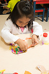 Education preschool 3 year olds girl applying gluing object for collage with feathers art activity