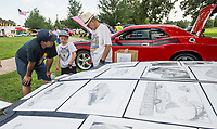 NWA Democrat-Gazette/BEN GOFF @NWABENGOFF<br /> Jon Nelson (from left) and son Levi Sullins, 9, of Gentry buy artwork by Dannie Turner of Strange Kat Art from Springdale during the car show Thursday, July 4, 2019, during the 125th annual Gentry Freedom Fest at Gentry City Park.