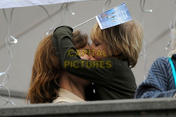 Viktor & Natalia Vodianova.The Russian Maslenitsa in Trafalgar Square, London, England..February 26th, 2012.**EXCLUSIVE ALL-ROUNDER**.headshot portrait half length carrying holding kid child mother mom mum son family funny flag profile kiss kissing .CAP/IA.©Ian Allis/Capital Pictures.