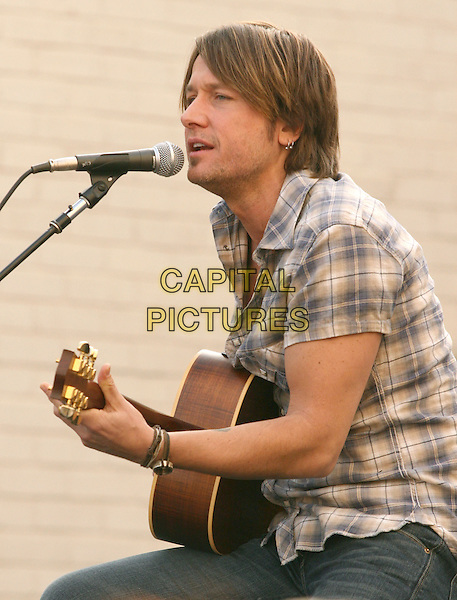 KEITH URBAN.is joined by Verizon Wireless and Samsung Mobile as he makes an in-store appearance for his fans at the Verizon Wireless store in Pasadena, California, USA, November 21st 2009                                                                   .half length music concert gig live on stage grey gray brown plaid checked check shirt microphone playing tattoo bracelets singing profile sitting jeans guitar .CAP/RKE/DVS.©DVS/RockinExposures/Capital Pictures