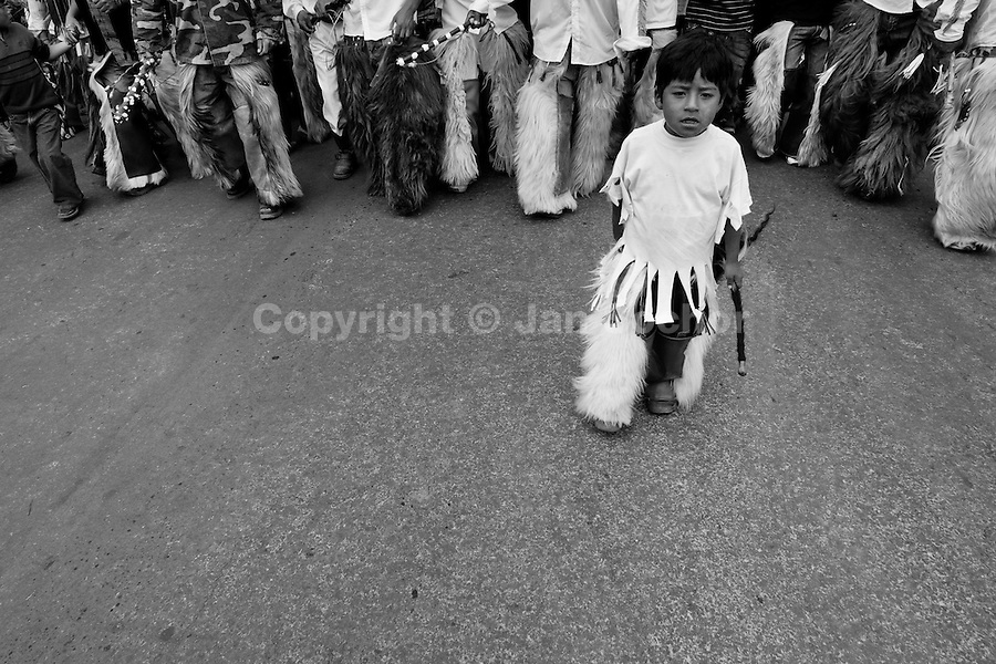 An Indian boy, wearing goatskin chaps, walks at the head of the dancing group during the Inti Raymi (San Juan) festivities in Cotacachi, Ecuador, 24 June 2010. 'La toma de la Plaza' (Taking of the square) is an ancient ritual kept by Andean indigenous communities. From the early morning of the feast day, various groups of San Juan dancers from remote mountain villages dance in a slow trot towards the main square of Cotacachi. Reaching the plaza, Indians start to dance around. They pound in synchronized dance rhythm, shout loudly, whistle and wave whips, showing the strength and aggression. Dancers from either the upper communities (El Topo) or the lower communities (La Calera), joined in respective coalitions, seek to conquer and dominate the square and do not let their rivals enter. If not moderated by the police in time, the high tension between groups always ends up in violent clashes.