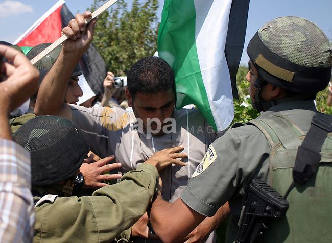 A demonstrator scuffle with Israeli soldiers during a demonstration by locals, left-wing Israelis, foreigner peace activists in Beit Omar, near the West Bank city of Hebron on August 20, 2011 against the latest Israeli air strikes on Gaza in which 14 people were killed and around 40 wounded, according to Palestinian sources. Photo by Najeh Hashlamoun.