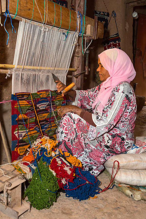 Morocco.  Berber Woman Weaving a Rug in her Home.  Ait Benhaddou Ksar, a World Heritage Site.